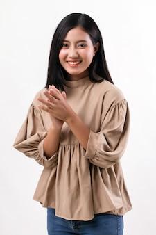 Gelukkige glimlachende vrouw die in haar hand klapt