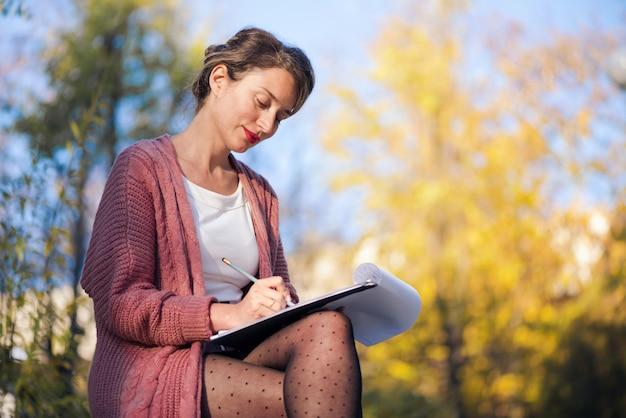 Gelukkige glimlachende vrouw die met documenten werkt en brieven schrijft