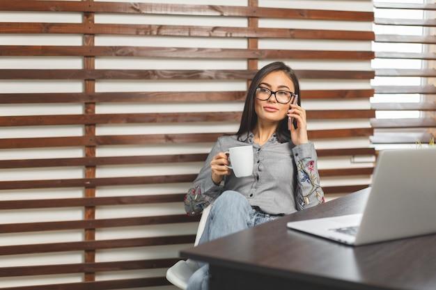 Gelukkige glimlachende vrouw die met laptop en het drinken koffie werkt