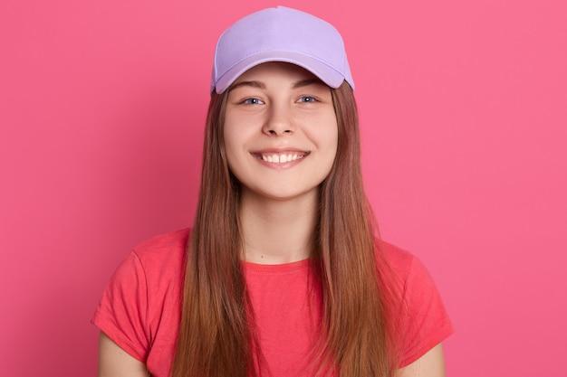 Gelukkige glimlachende vrouw die speels terwijl stellen geïsoleerd over roze muur kijkt, die rode t-shirt en honkbal glb draagt.