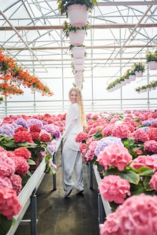 Gelukkige glimlachende vrouw die zich dichtbij mooie roze bloemen bevindt