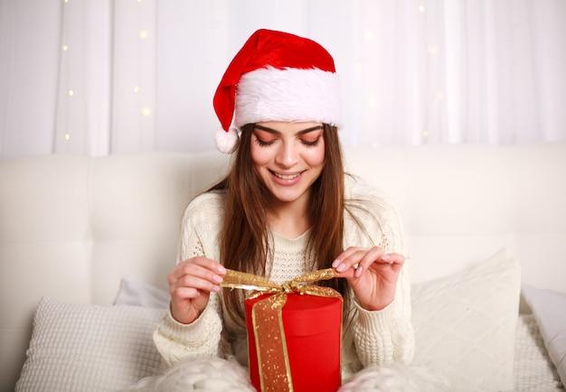 Gelukkige glimlachende vrouw in rode kerstmishoed met gift op bed thuis