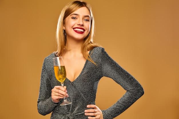 Gelukkige glimlachende vrouw in stijlvolle glamoureuze jurk met champagneglas.