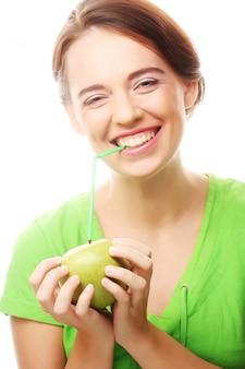 Gelukkige glimlachende vrouw met appel en rietcocktail