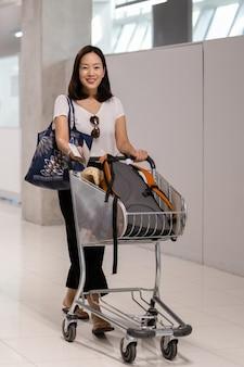 Gelukkige glimlachende vrouw met bagage in kar op de luchthaven.