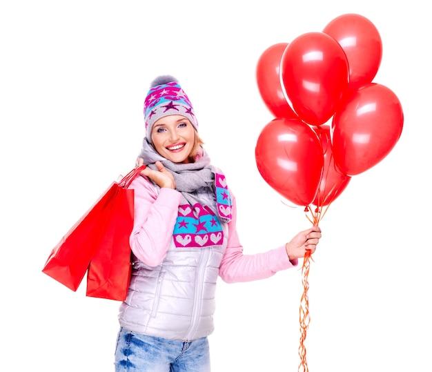 Gelukkige glimlachende vrouw met giften en rode ballons na het winkelen op wit wordt geïsoleerd