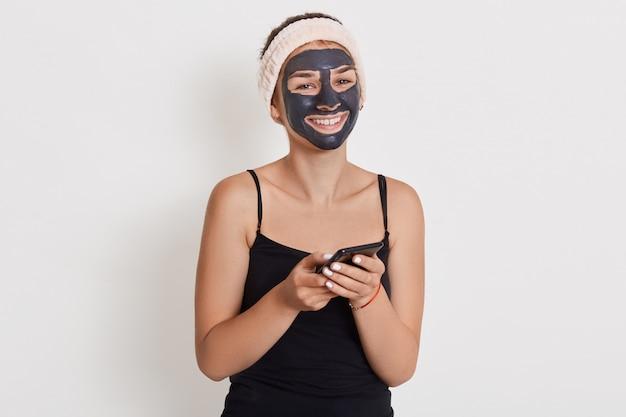 Gelukkige glimlachende vrouw met zwart kosmetisch masker met gelukkige blik, houdend telefoon, controlerend sociaal netwerk terwijl het doen van kosmetische procedures.