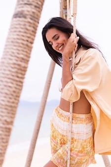 Gelukkige glimlachende vrouw op schommel bij strand, dag warm licht.