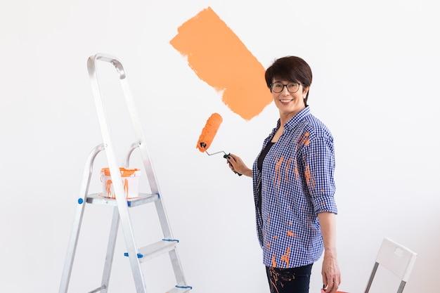 Gelukkige glimlachende vrouw van middelbare leeftijd schilderen binnenmuur van nieuw huis.