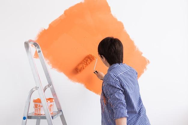 Gelukkige glimlachende vrouw van middelbare leeftijd schilderen binnenmuur van nieuw huis