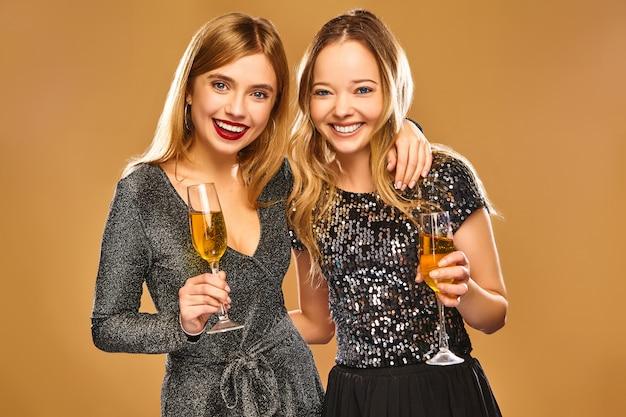 Gelukkige glimlachende vrouwen in stijlvolle glamoureuze jurken met champagneglazen
