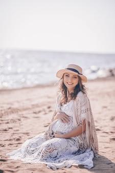 Gelukkige glimlachende zwangere vrouw op het strand