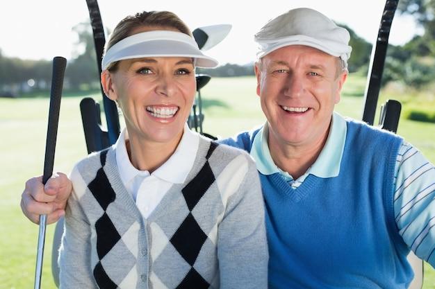 Gelukkige golfende paarzitting in golf met fouten die bij camera glimlachen