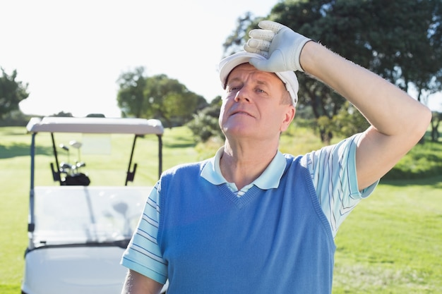 Gelukkige golfspeler die camera met erachter golf met fouten bekijkt