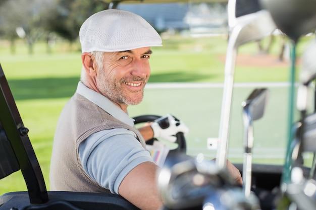 Gelukkige golfspeler die zijn golf met fouten rijden die bij camera op een zonnige dag bij de golfcursus glimlachen