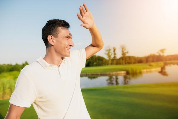 Gelukkige golfspeler in witte kleding in de zon.