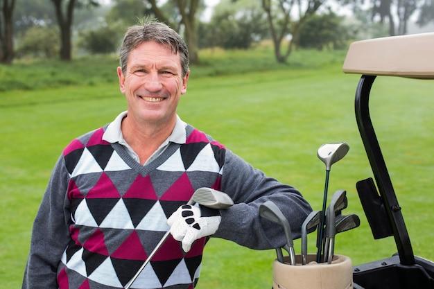 Gelukkige golfspeler naast zijn golf met fouten