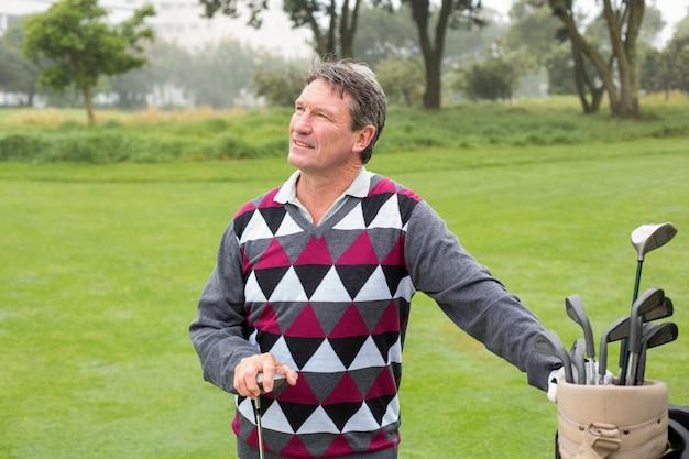 Gelukkige golfspeler naast zijn golftas