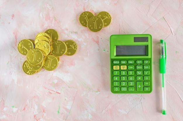 Gelukkige gouden chocolademunten, groene rekenmachine en pen op roze
