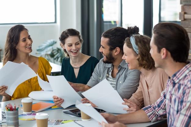 Gelukkige grafische ontwerpers die tijdens het bespreken in vergadering lachen