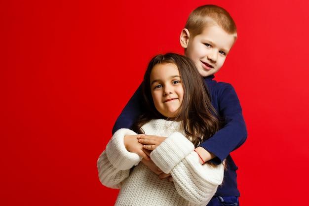 Gelukkige grappige kinderen staan samen en omarmen geïsoleerd op rood