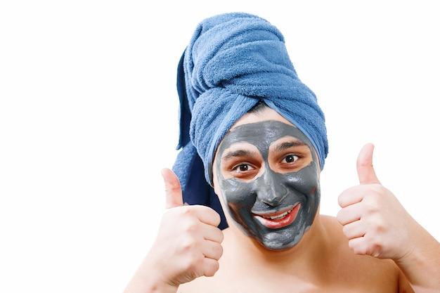 Gelukkige grappige man met masker voor de huid, man maakt graag een masker voor de huid, man toont klasse, blauwe handdoek op het hoofd, geïsoleerde foto,