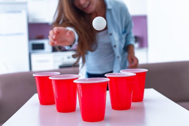 Gelukkige grappige vrouw die met dranken thuis van bier pong spel op lijst genieten