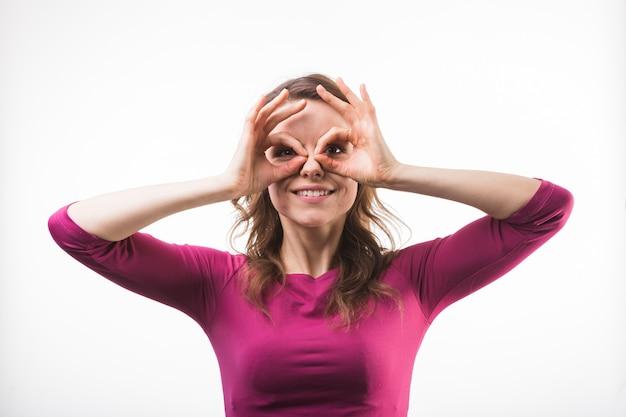 Gelukkige grappige vrouw die met verrekijkershanden camera bekijken