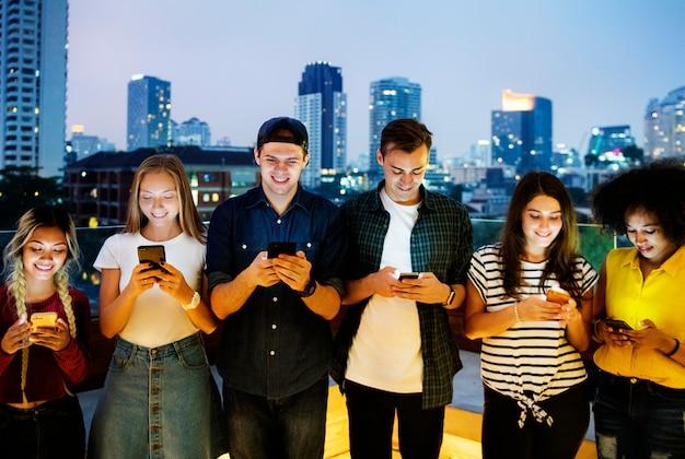 Gelukkige groep jonge volwassenen die smartphones in cityscape gebruiken