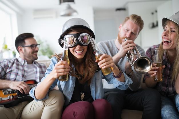 Gelukkige groep leuke en vrolijke vrienden die instrumenten bespelen en feesten