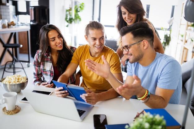 Gelukkige groep studenten, vrienden die studeren om samen te werken en plezier te hebben