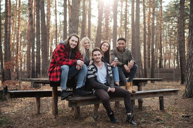 Gelukkige groep vrienden die in openlucht in het bos zitten.