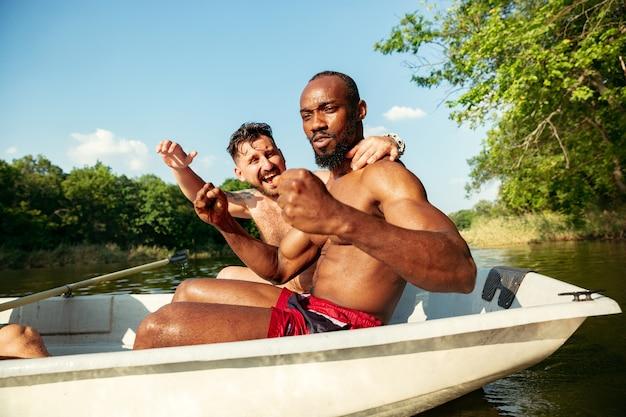 Gelukkige groep vrienden die plezier hebben tijdens het lachen, opspattend water en zwemmen in de rivier