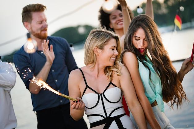 Gelukkige groep vrienden die samen buiten feesten en plezier hebben