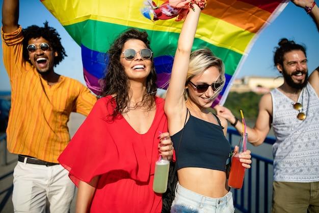 Gelukkige groep vrienden, mensen wonen een gay pride-evenement bij