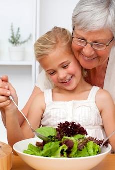 Gelukkige grootmoeder die een salade met kleindochter kookt