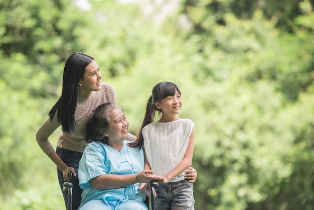 Gelukkige grootmoeder in rolstoel met haar dochter en kleinkind in een park, gelukkig leven gelukkig tijd.