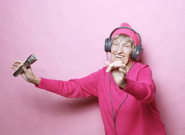 Gelukkige grootmoeder met hoofdtelefoons en microfoon over roze achtergrond