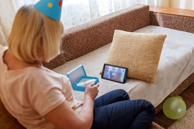Gelukkige grootmoeder viert verjaardag samen met haar familie via internet in quarantainetijd