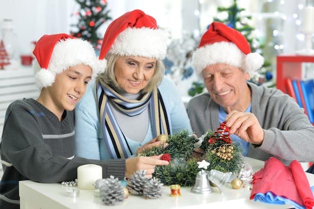 Gelukkige grootouders met hun tienerkleinzoon die zich thuis voorbereiden op kerstmis