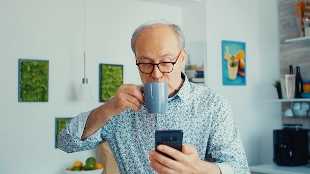 Gelukkige grootvader die muziek luistert en danst tijdens het ontbijt in de keuken met een bril ontspannen oudere senior dansen, leuke levensstijl met moderne technologie