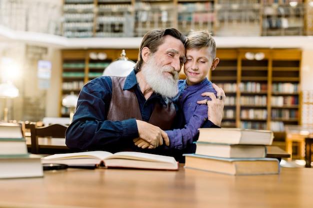 Gelukkige grootvader en kleinzoon omhelzen elkaar terwijl ze samen tijd doorbrengen in vintage oude bibliotheek, boeken lezen
