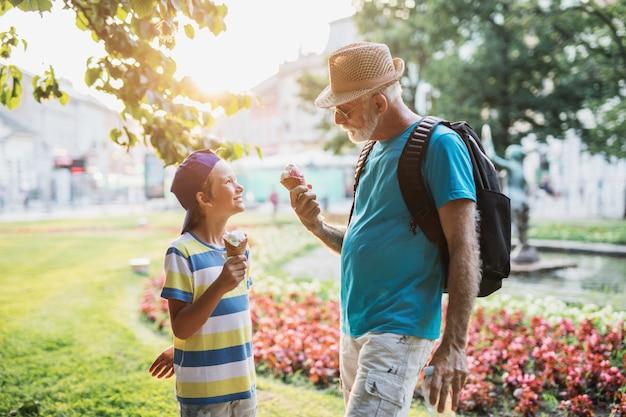 Gelukkige grootvader geniet met zijn kleinzoon terwijl hij buiten ijs eet in het park.
