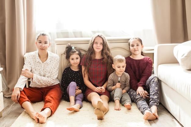 Gelukkige grote familie van broers en zussen die op de grond zitten