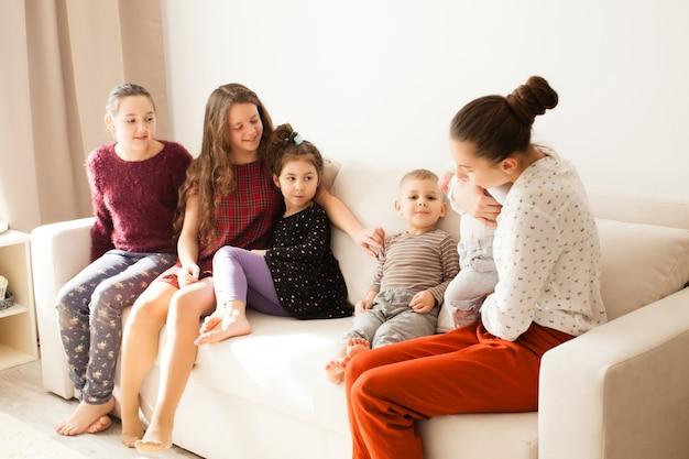 Gelukkige grote familie van broers en zussen zittend op de bank in witte kamer