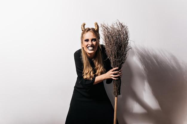 Gelukkige heks die met grappig kapsel haar bezem houdt. binnen schot van opgewonden meisje in halloween-kostuum dat zich op witte muur bevindt.