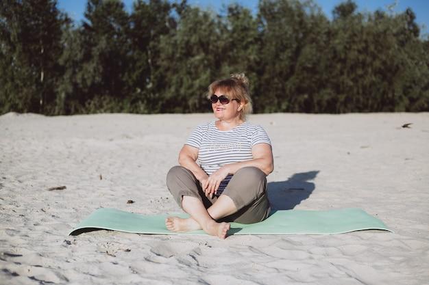 Gelukkige het glimlachen hogere vrouwenzitting op een zand op zonnige dag