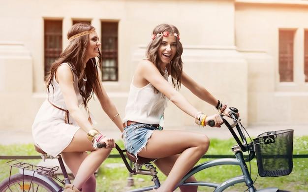 Gelukkige hippievrouw veel plezier tijdens het rijden op een tandem