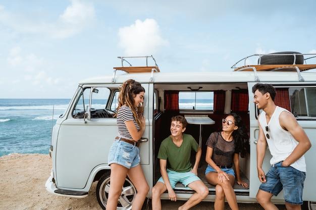 Gelukkige hipster genieten van vakantie terwijl ze leunen op hun vintage busje