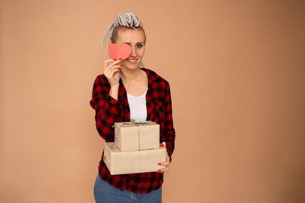Gelukkige hipster jonge vrouw op sint-valentijnsdag met geschenkdozen en rood hart valentijn geïsoleerd op beige achtergrond